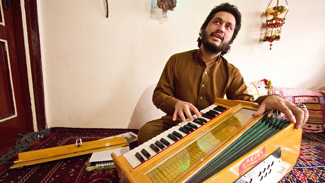 PHOTO: 23-year old Naweed Forugh, a former winner of Afghanistans version of American Idol, plays the harmonia, a traditional Afghan musical instrument, in his living room. After nearly losing his life to an unknown gunman, Forugh is too afraid to leave