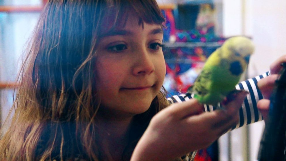 Aelita Andre pictured with Greengrass, one of her pet birds.