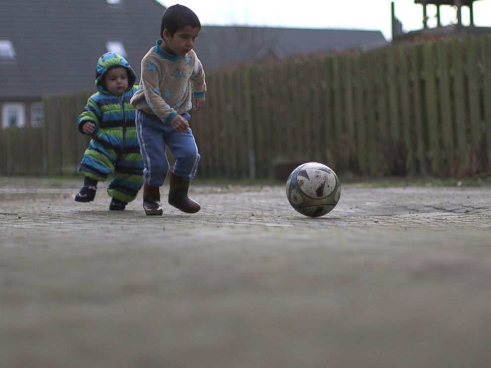 PHOTO: Houmideh and Fahed play soccer outside their new home in Hattstedt, Germany.