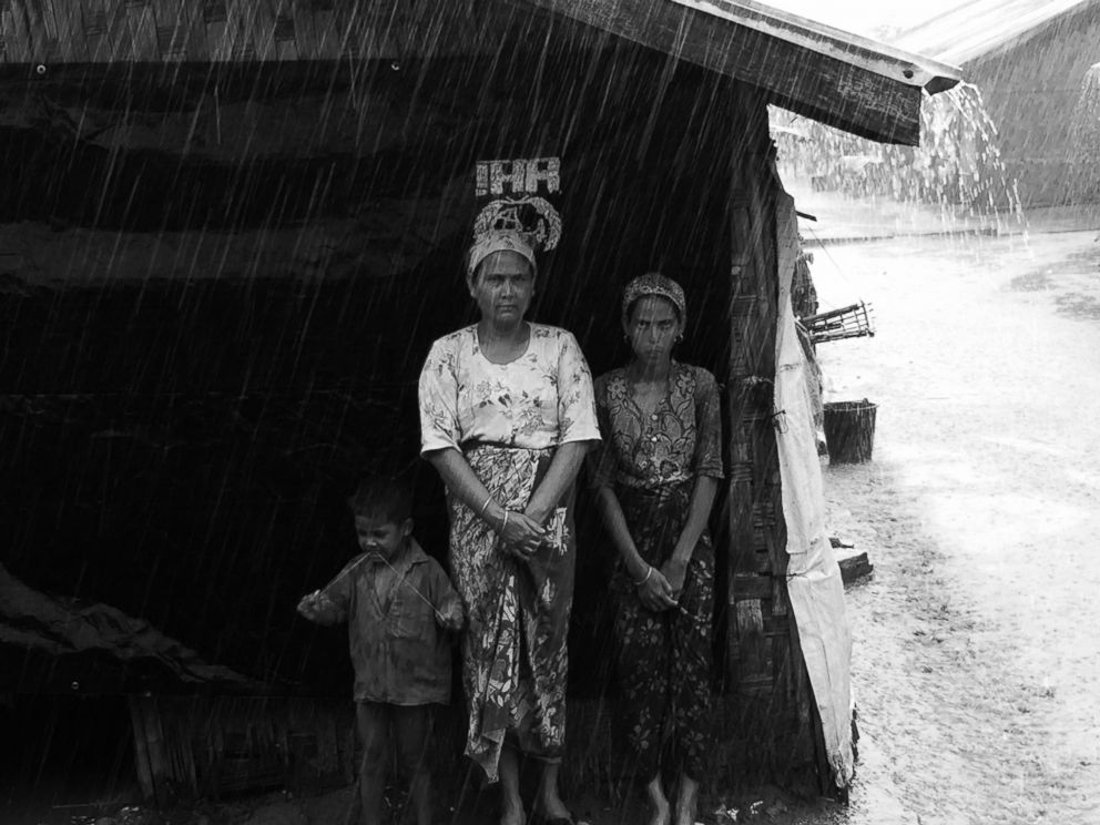 PHOTO: Rohingya women are pictured in a refugee camp on the outskirts of Sittwe, Myanmar, waiting for the rain to stop.