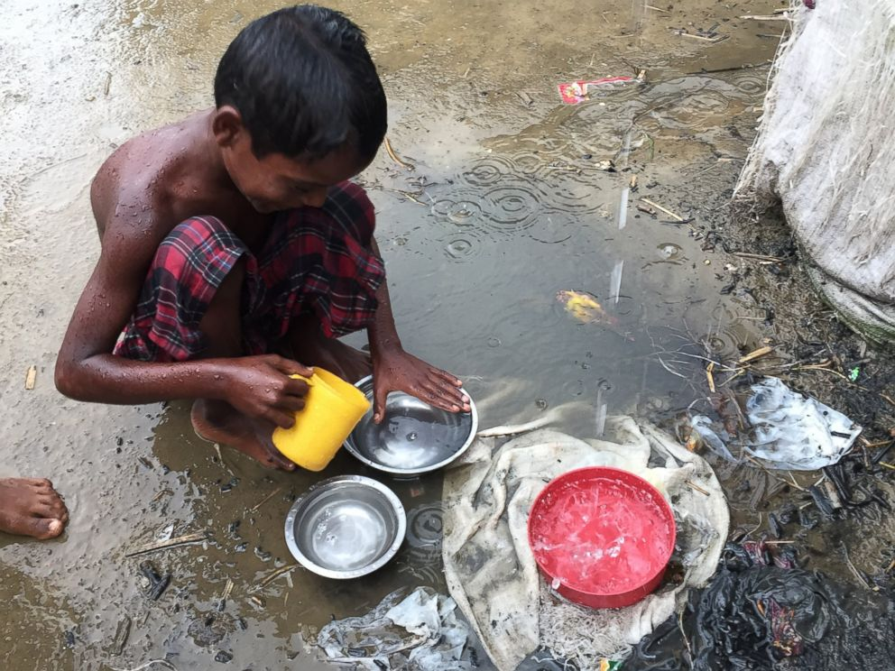 PHOTO: A young Rohingya boy in the refugee camp using rainwater to rinse dishes.