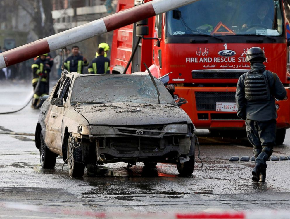 PHOTO: Police officers keep watch while a man drives his heavily damaged car at a car bomb attack site in Kabul, Afghanistan, Jan. 27, 2018.