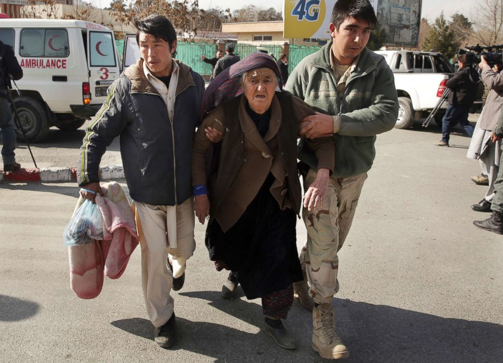 An wounded elderly woman is assisted at the site of a deadly suicide attack in the center of Kabul, Afghanistan, Jan. 27, 2018.