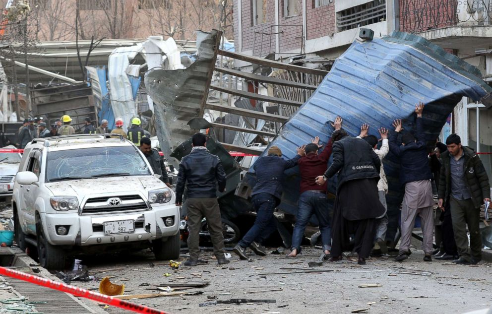 People try to remove debris from the scene of a suicide bomb attack in Kabul, Afghanistan, Jan. 27, 2018.