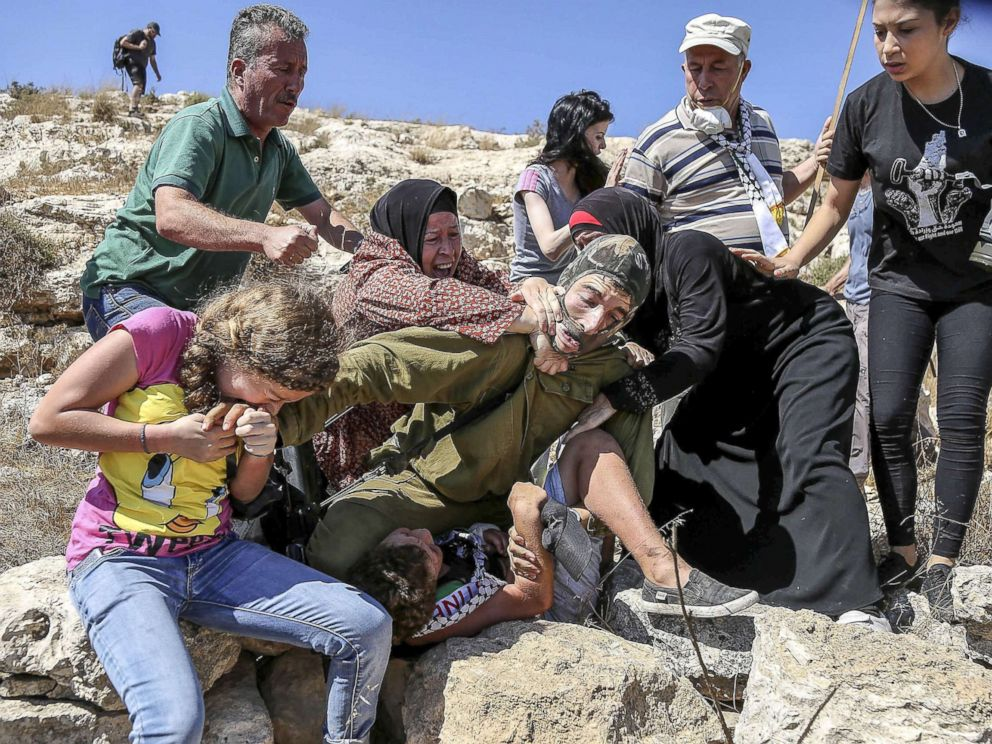 PHOTO: Ahed Tamimi reacts to an Israeli soldier attempts to arrest a Palestinian kid during the clashes following a protest against expropriation of Palestinian land in the West Bank, Aug.28, 2015.