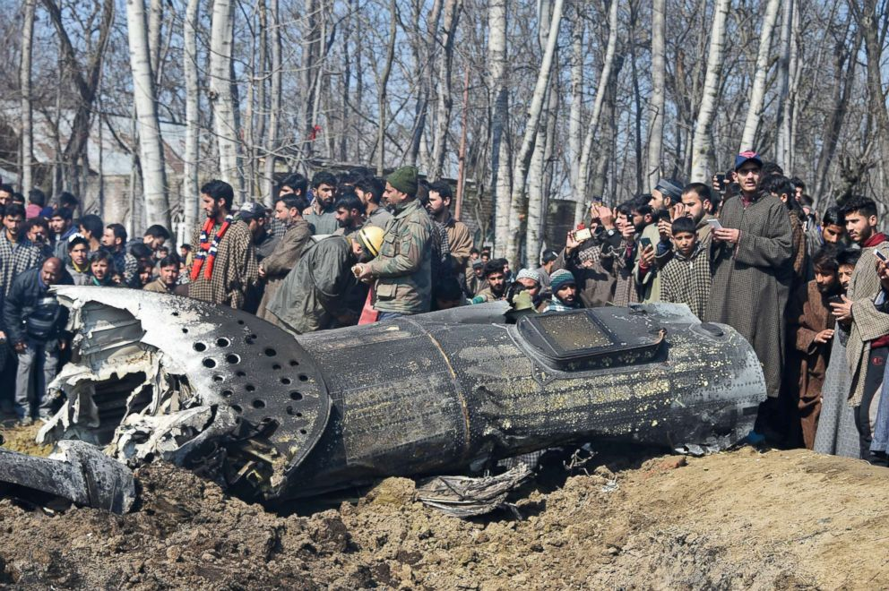 PHOTO: Indian soldiers and Kashmiri onlookers stand near the remains of an Indian Air Force helicopter after it crashed in Budgam district, on the outskirts of Srinagar on Feb. 27, 2019.