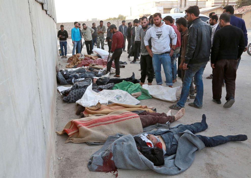PHOTO: People gather next to bodies following a reported airstrike on the rebel-held town of Atareb in Syrias northern Aleppo province, Nov. 13, 2017.