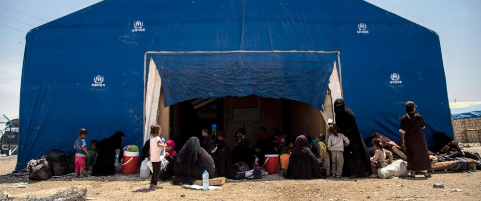 PHOTO: Women and children related to fighters of the Islamic State group wait to board buses and trucks, leaving the overcrowded al-Hol camp to return to their homes, June 3, 2019, in Hasakeh, Syria.