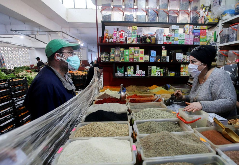 A vendor wearing a protective face mask serves a customer inside her shop, ahead of the Muslim holy month of Ramadan, amid concerns over the coronavirus disease (COVID-19), in Algiers, Algeria, April 19, 2020.Ramzi Boudina/Reuters