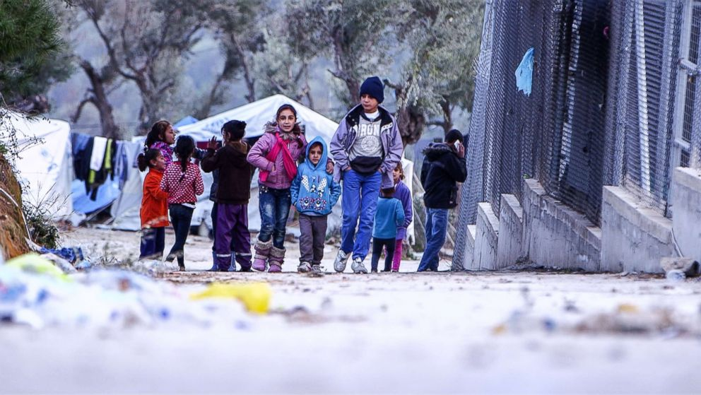 PHOTO: Anas Hommada, 14, and his younger siblings walk in Lesbos Moria refugee camp.