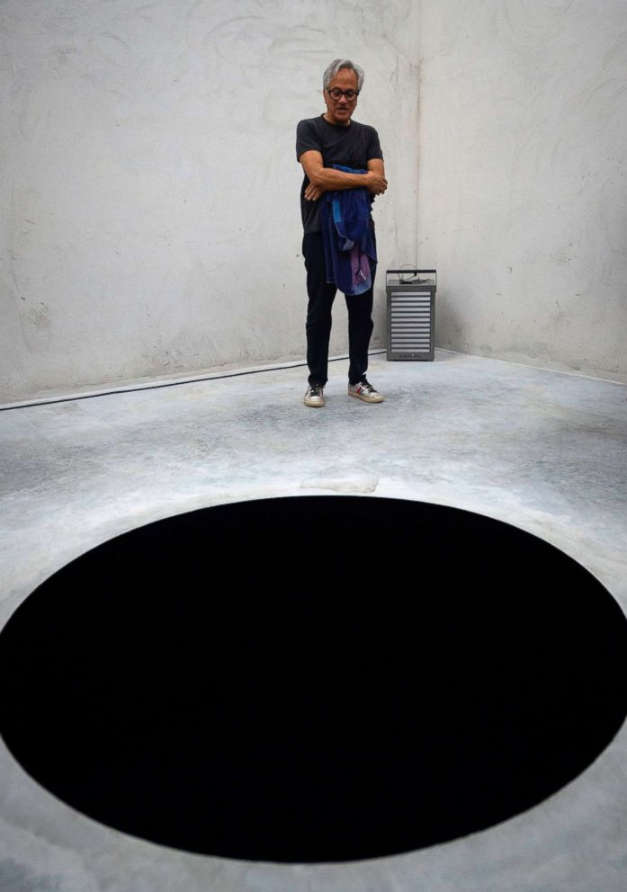 PHOTO: Anish Kapoor stands next his artwork Descent into limbo during the opening of his exhibition entitled Works, thoughts, experiments at the Serralves Foundation in Porto, on July 6, 2018.