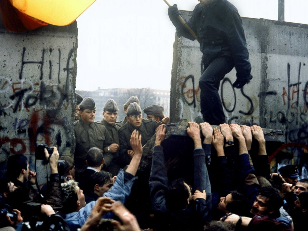 PHOTO: East German border guards are pictured through the gap after crowds tear down a section of the Berlin Wall in Germany, Nov. 10, 1989.