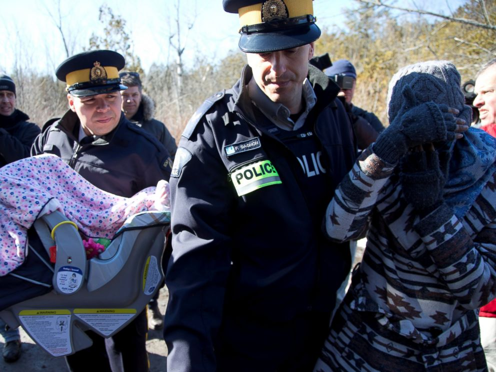 PHOTO: A mother and her child are taken into custody by Royal Canadian Mounted Police officers after crossing U.S.-Canada border into Hemmingford, Quebec, Feb. 20, 2017.