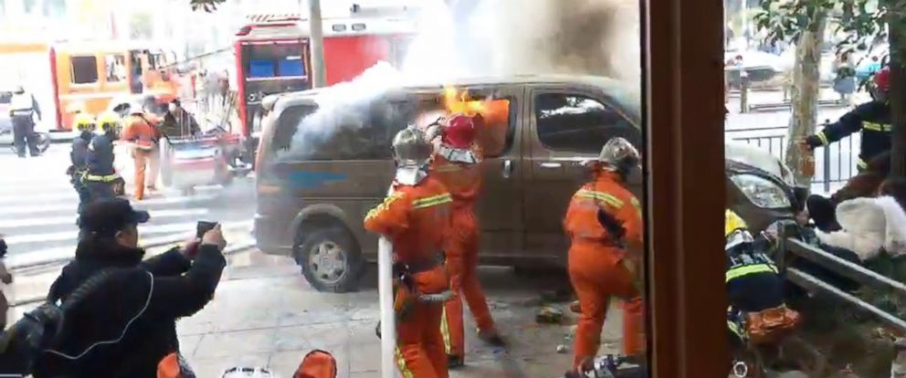 In this image taken from cellphone video provided to the Associated Press, firefighters put out a blaze after a minivan carrying gas tanks plowed into pedestrians along a street in Shanghai, Friday, Feb. 2, 2018.