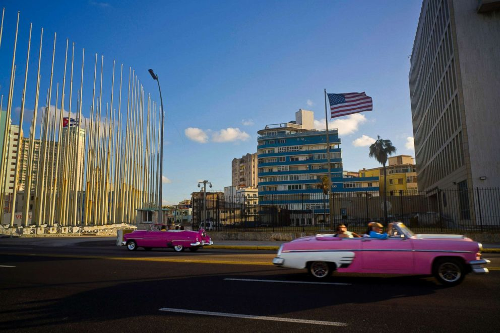 PHOTO: Tourists ride in classic American convertible cars past the United States embassy in Havana, Cuba, Jan. 12, 2017.