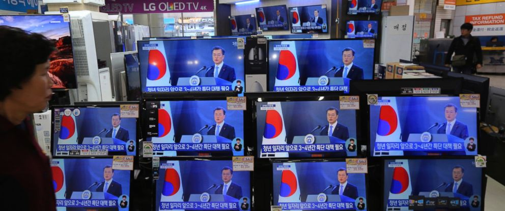A woman watches TV screens showing the live broadcast of South Korean President Moon Jae-ins New Years speech at the Yongsan Electronic store in Seoul, South Korea, Wednesday, Jan. 10, 2018.
