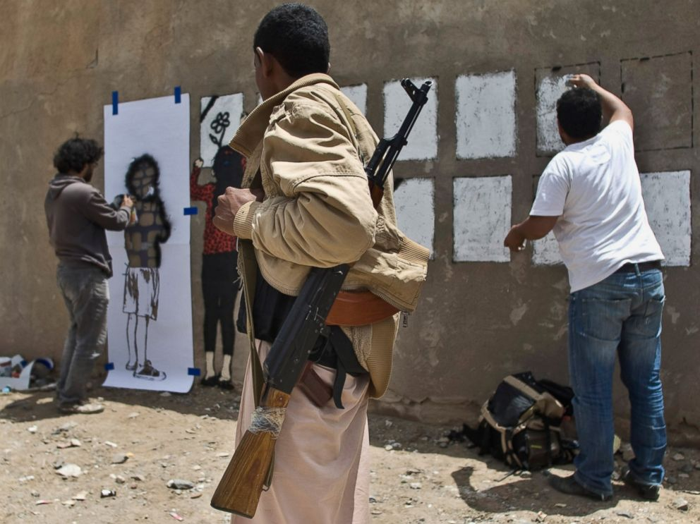 PHOTO: An armed man looks at Murad Subay and a collaborator spraying graffiti on a wall to commemorate the victims who were killed in Saudi-led coalition airstrikes in Sanaa, Yemen, May 18, 2015.