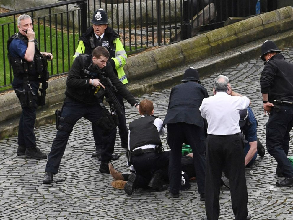PHOTO: A policeman points a gun at a man on the ground as emergency services attend the scene outside the Palace of Westminster, London, March 22, 2017.