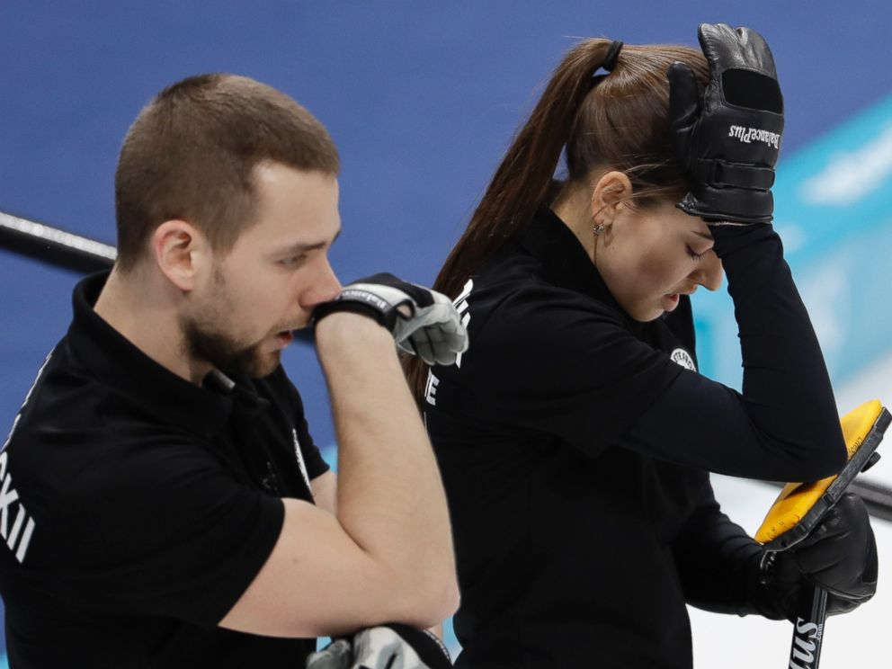 Russian athletes Anastasia Bryzgalova, right, and Aleksandr Krushelnitckii look down during the mixed doubles semi-final curling match against Switzerland Jenny Perret and Martin Rios at the Winter Olympics in South Korea, Monday, Feb. 12, 2018.