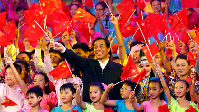 """PHOTO: In this photo taken on Sept. 29, 2011, Bo Xilai, party boss of Chongqing, center, and others wave Chinese flags during a gathering to promote the singing of """"red songs"""" in southwest China's Chongqing Municipality."""