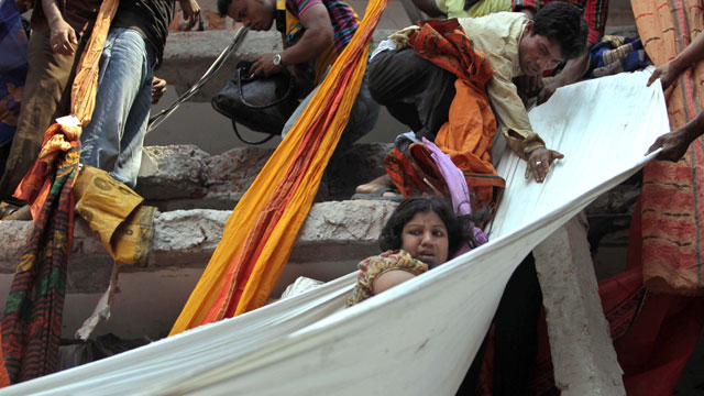 PHOTO:Rescue workers use pieces of clothes to bring down a survivor after an eight-story building housing several garment factories collapsed in Savar, near Dhaka, Bangladesh, Wednesday, April 24, 2013.