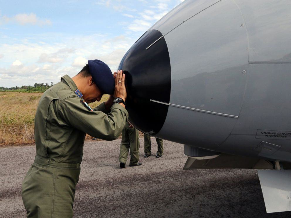 PHOTO: A crew member of Indonesian Navy CN-235 airplane prays prior to the start of a search operation for the missing AirAsia flight 8501 at the airport in Pangkal Pinang, Bangka Island, Indonesia, Dec. 30, 2014.