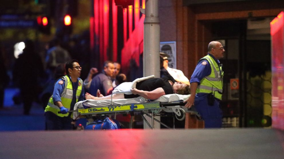 A injured hostage is wheeled to an ambulance after shots were fired during  a cafe  siege at Martin Place in the central business district of Sydney, Australia, Dec. 16, 2014.