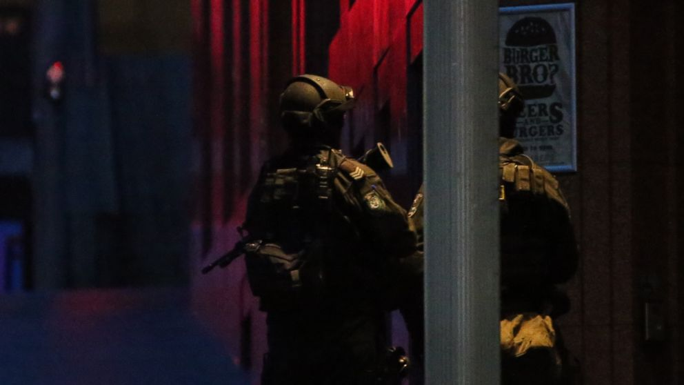 Armed tactical response police personnel stand watch into the evening near a cafe under siege by a gunman at Martin Place in the central business district of Sydney, Australia, Dec. 15, 2014.
