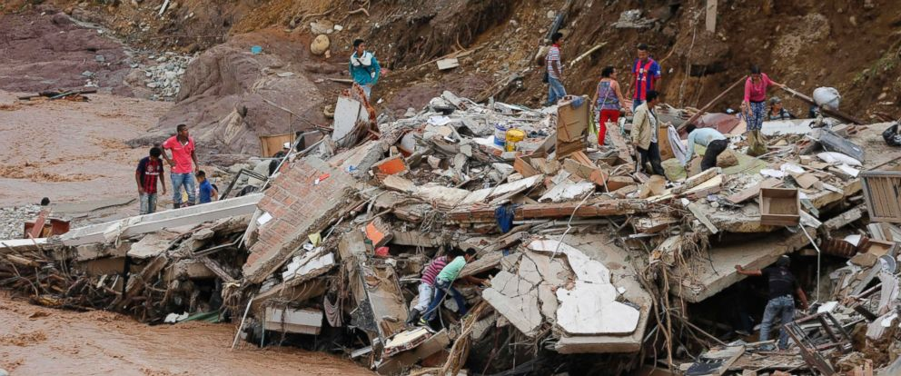 PHOTO: People walk over the debris of a collapsed building in Mocoa, Colombia, Sunday, April 2, 2017. Colombias President Juan Manuel Santos declared Mocoa a disaster area.