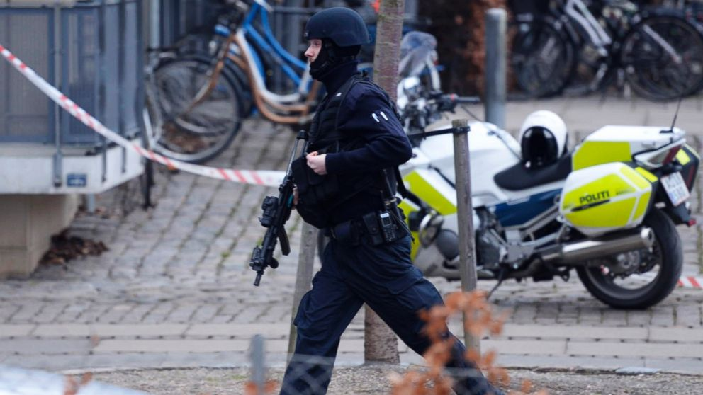 "An armed security officer runs down a street near a venue after shots were fired where an event titled  ""Art, blasphemy and the freedom of expression"" was being held in Copenhagen, Saturday, Feb. 14, 2015."