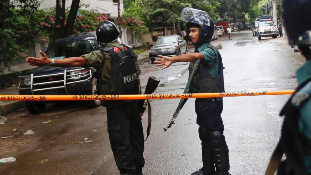 Bangladeshi policemen clear out an area to facilitate action against heavily armed militants who struck at the heart of Bangladesh's diplomatic zone on Friday night, taking dozens of hostages at a restaurant popular with foreigners, Dhaka, Bangladesh, Saturday, July 2, 2016. Police sustained casualties and dozens of people were wounded in a gun battle as security forces cordoned off the area and sought to end the standoff.