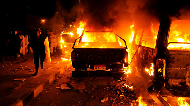 PHOTO: A riot policeman passes burning vehicles during clashes outside the U.S. embassy in Cairo, Egypt, early Thursday, Sept. 13, 2012, as part of widespread anger across the Muslim world about a film ridiculing Islams Prophet Muhammad.