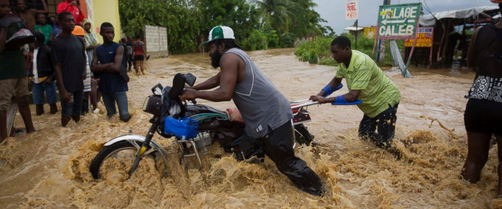 PHOTO: Two men push a motorbike through a street flooded by a nearby river that overflowed from heavy rains caused by Hurricane Matthew, in Leogane, Haiti, Oct. 5, 2016.