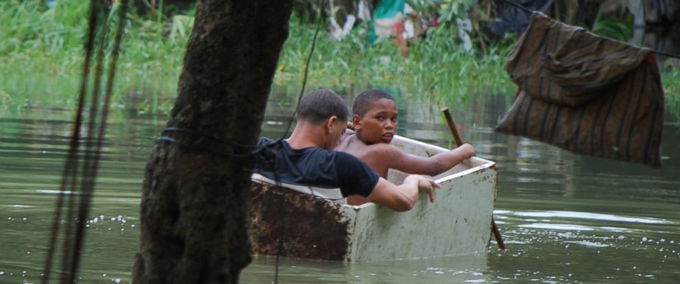PHOTO: Two boys float in an old wooden box in an area flooded by heavy rains caused by Hurricane Matthew, in La Puya slum, in the Arroyo Hondo creek in Santo Domingo, Dominican Republic, Oct. 4, 2016.