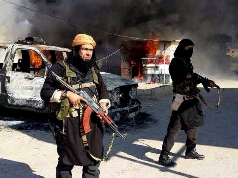PHOTO: This undated file image posted on a militant website on Jan. 4, 2014, shows a senior member of ISIS next to a burning police vehicle in Iraqs Anbar Province.