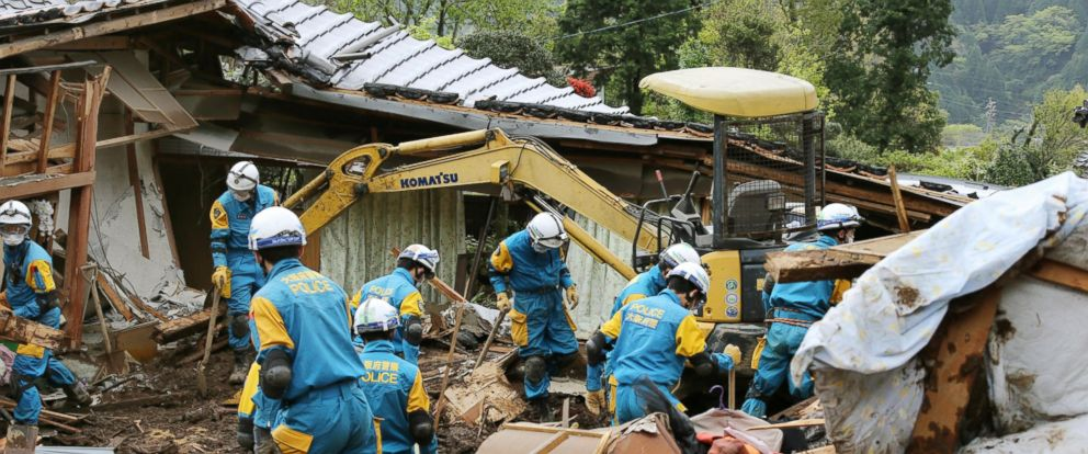 PHOTO: Police officers search for missing persons near houses destroyed by landslide in Minamiaso, Kumamoto prefecture, Japan Sunday, April 17, 2016.