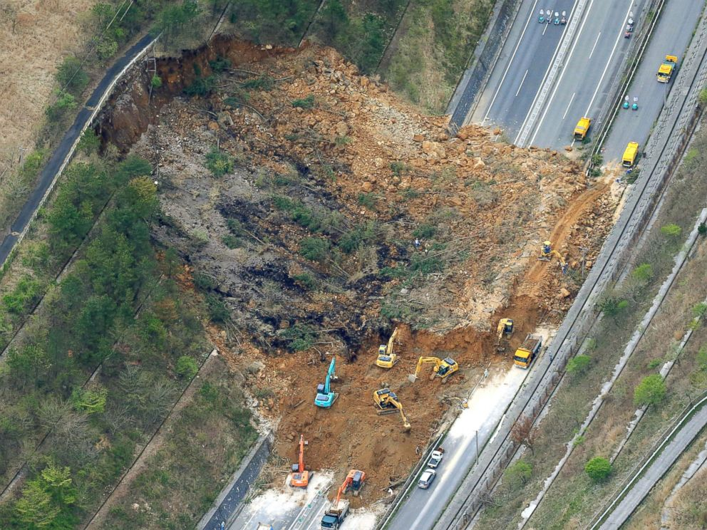 PHOTO: Heavy machinery works recovery efforts of Oita Expressway damaged by a landslide following an earthquake in Yufu, Oita prefecture, Japan, April 16, 2016.