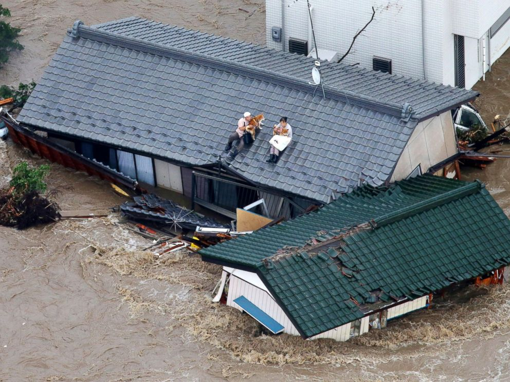 PHOTO: Residents holding dogs wait for help, sitting on the roof of their house in the flooded city of Joso, Ibaraki prefecture, northeast of Tokyo, Sept. 10, 2015.