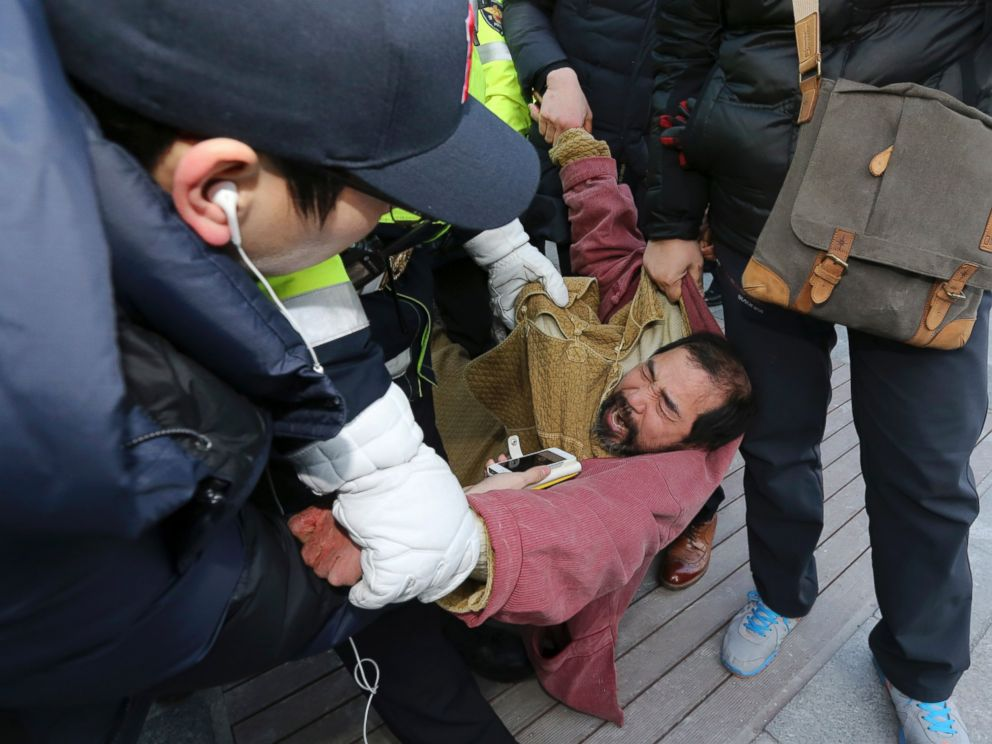 PHOTO: A suspect, center, identified by police as 55-year-old Kim Ki-jong, is detained by police officers in Seoul, South Korea, March 5, 2015.