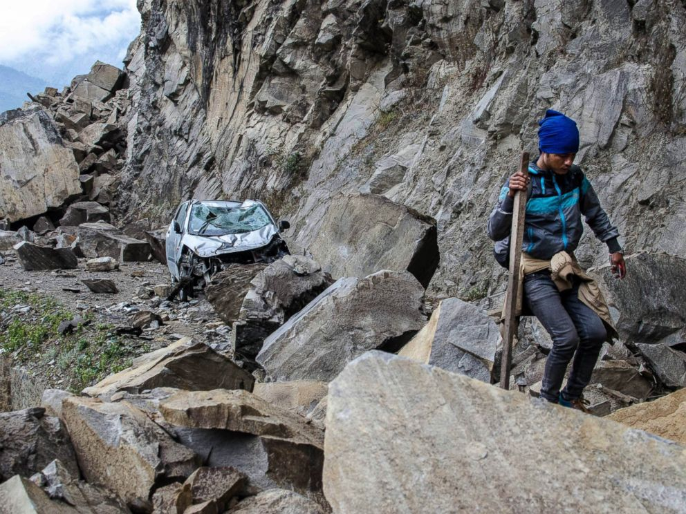 PHOTO: In this April 27, 2015 photo, a Nepalese man walks over fallen rocks and past a crushed car on the way to Dhunche, Nepal, a village in Langtang National Park, two days after a 7.8-magnatude earthquake hit the region.