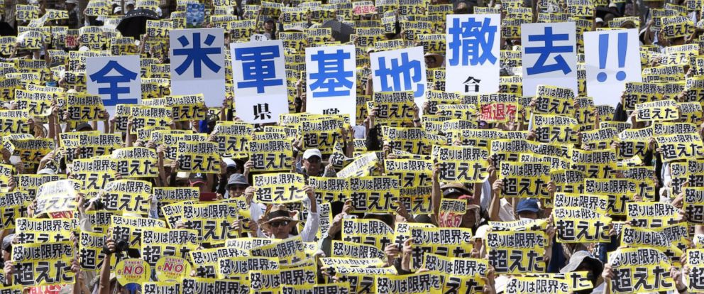 "PHOTO: Protesters hold placards that read: ""Our anger went over our own limit"" and ""Remove all U.S. bases!!"" during a protest rally against the presence of U.S. military bases on the southwestern island of Okinawa in Naha, Okinawa, June 19, 2016."