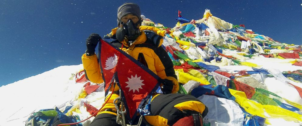 PHOTO: In this May 20, 2013 file photo, Nepalese climber Pasang Geljen Sherpa holds a flag of Nepal and rests on top of the 29,035-foot Mount Everest, surrounded by Tibetan prayer flags.