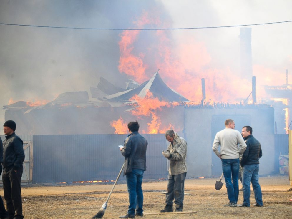 PHOTO: People watch burning houses in the village of Smolenka, Russia, April 13, 2015.