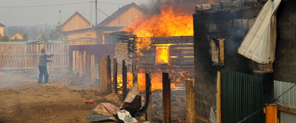 PHOTO: A man tries to save his house from fires spreading from burning neighboring homes in the village of Smolenka, Russia, April 13, 2015.