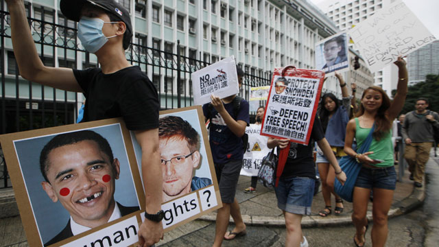 PHOTO:A supporter holds a picture of U.S. President Barack Obama and Edward Snowden, a former CIA employee who leaked top-secret information about U.S. surveillance programs during a demonstration outside the Consulate General of the United States in Hon