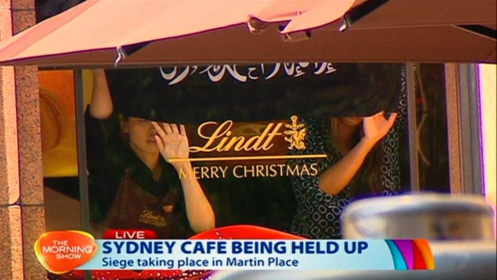 This image taken from video show people holding up what appeared to be a black flag with white Arabic writing on it, inside a cafe in Sydney, Australia, Dec. 15, 2014.