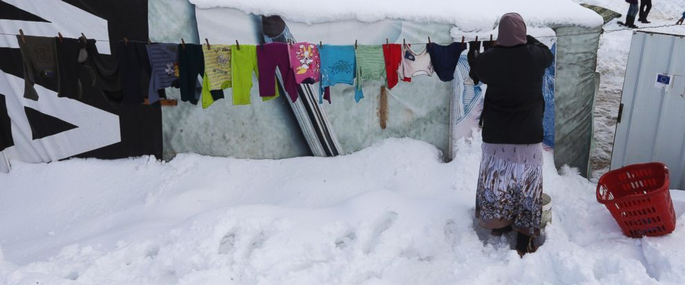PHOTO: A Syrian woman hangs her laundry outside her tent covered by snow at a refugee camp in Zahleh town, Bekaa valley, east Lebanon, Jan. 8, 2015.
