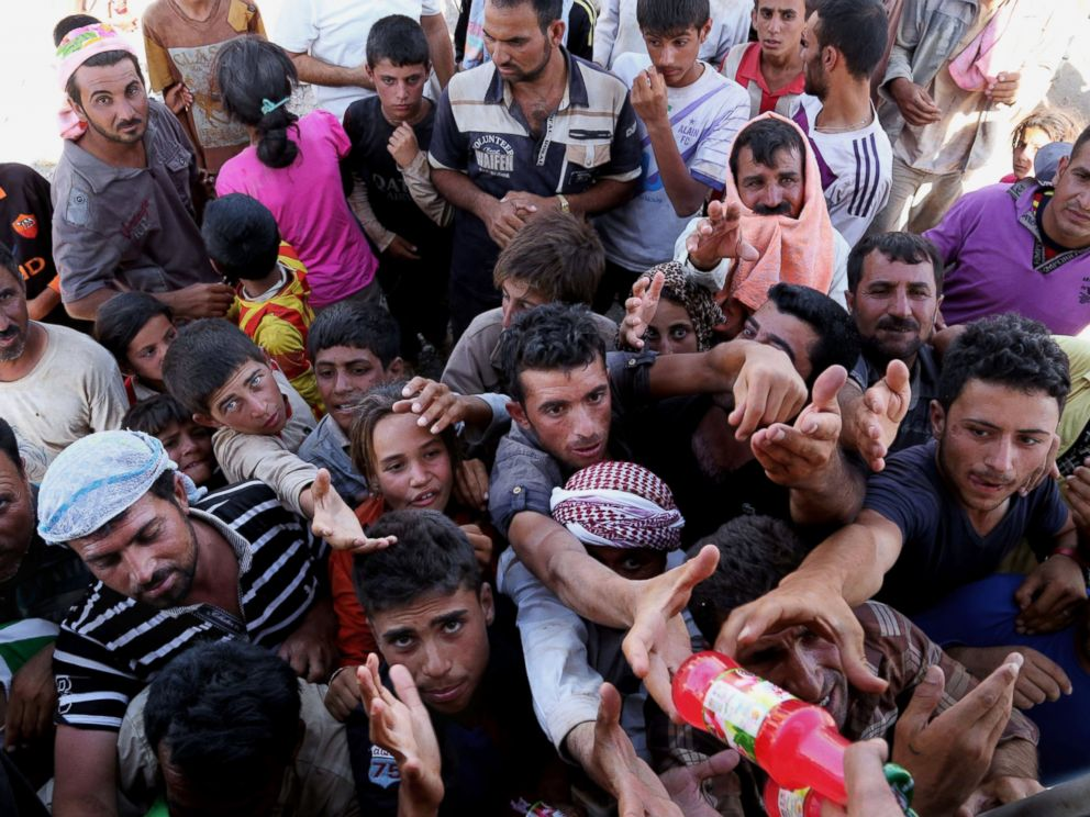 PHOTO: Displaced Iraqis from the Yazidi community gather for humanitarian aid at the Iraq-Syria border at Feeshkhabour border point on August 10, 2014.