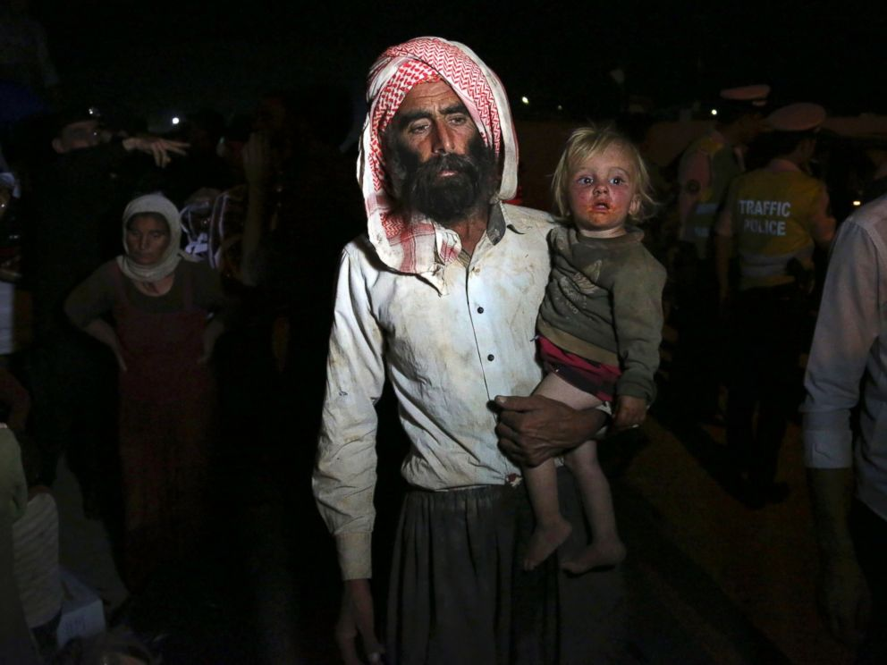 PHOTO: Displaced Iraqis from the Yazidi community cross the Syria-Iraq border at Feeshkhabour border point, in northern Iraq, Aug. 10, 2014.