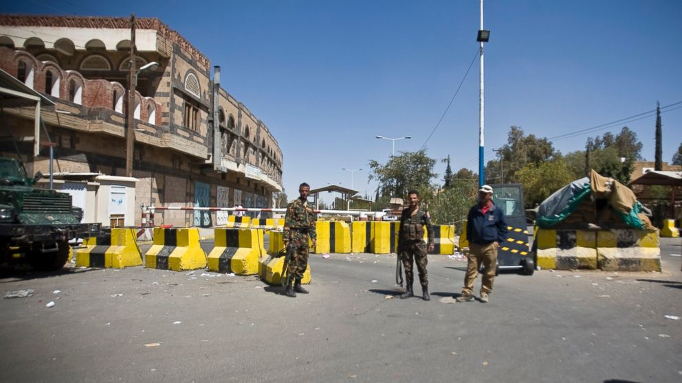 Police troopers stand guard at the entrance of the U.S. Embassy in Sanaa, Yemen, Feb. 11, 2015.